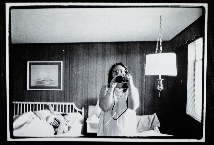 Auorretrato de la fotógrafa Elsa Dorfman frente al espejo con su marido Harvey acostado en e fondo. Fotograma del documental de Netflix 'The B-side: Elsa Dorfman's Portrait Photography'