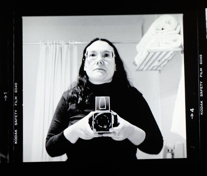 Autorretrato en blanco y negro de la fotógrafa Elsa Dorfman y su Hasselblad frente al espejo. Fotograma del documental de Netflix 'The B-side: Elsa Dorfman's Portrait Photography'