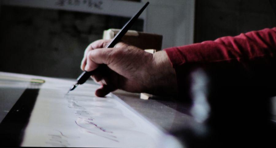 La mano de Elsa Dorfman mientras escribe en la parte inferior de una de sus Polaroids 20x24. Fotograma del documental de Netflix 'The B-side: Elsa Dorfman's Portrait Photography'