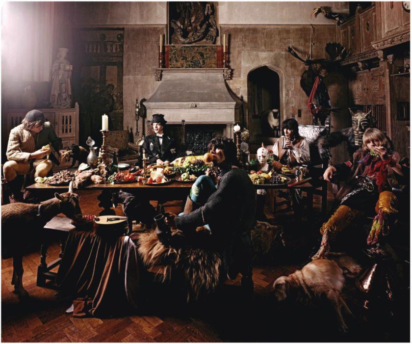 Los Rolling Stones vestidos de mendigos alrededor de una mesa llena de comida. Foto del fotógrafo Michael Joseph.