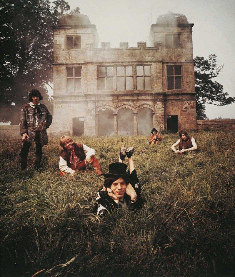 Los Rolling Stones tumbados en la hierba con un caserón en llamas al fondo para la foto que iba a ser la portada de Beggars Banquet. Foto: Michael Joseph.