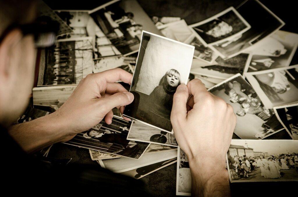 Un hombre observa un montón de fotos en blanco y negro. Imagen gratuita no sujeta a derechos de autor