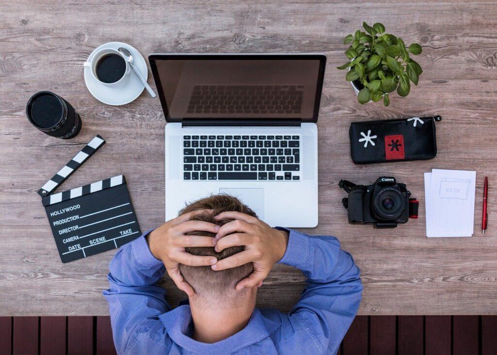 Imagen de un hombre que se lleva las manos a la cabeza ante un ordenador portátil. Fotografía gratuita no sujeta a derechos de autor.