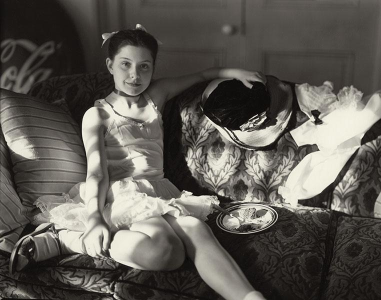 Niña de 12 años posando en un sofá fotografiada por Sally Mann para el libro At Twelve