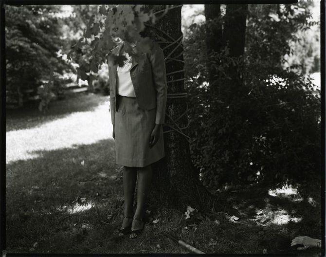 Foto de una niña de 12 años apoyada en un árbol y vestida como una persona mayor. Su cara está oculta por las ramas y un ojo asoma por uno de los huecos. Foto de Sally Mann para At Twelve.