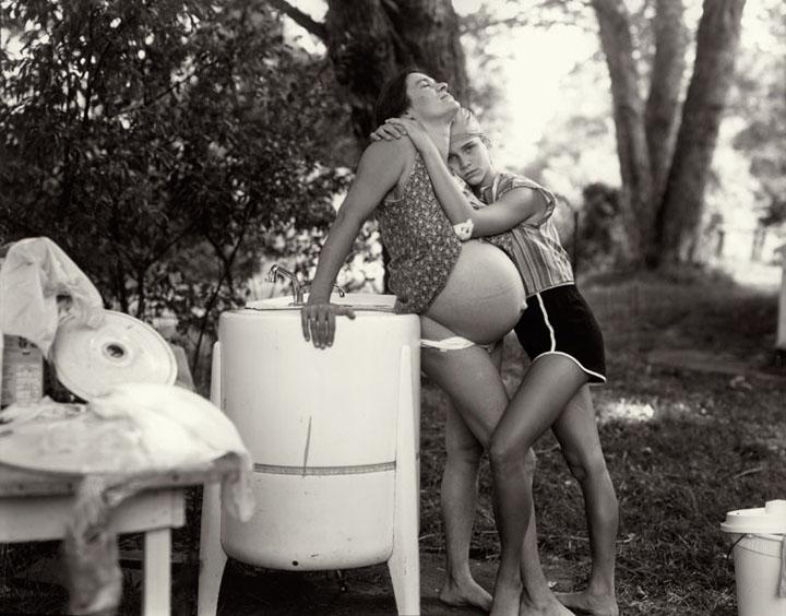 Niña de 12 años abraza a su madre embarazada que tiene el vientre al aire. Fotografía de Sally Mann para el libro At Twelve