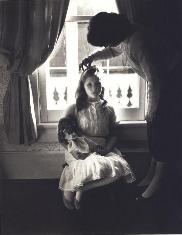 Niña de 12 años sentada de espaldas a una ventana con una muñeca en brazos y su madre arreglándole el pelo fotografiada por Sally Mann para el libro At Twelve