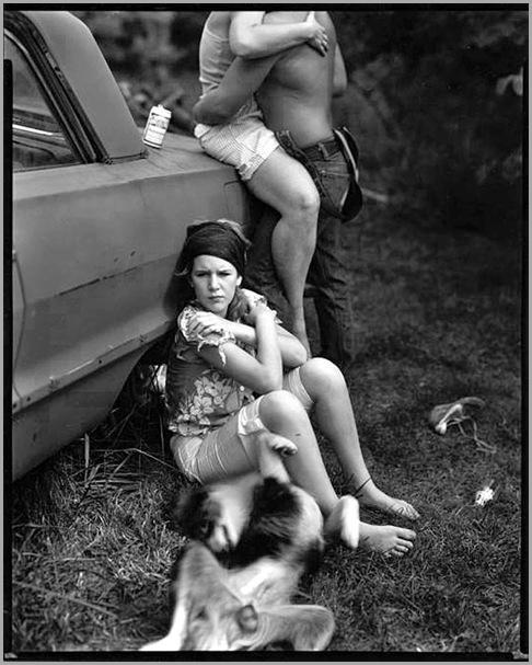 Niña de 12 años sentada en el suelo con las espalda apoyada en un coche en el que una pareja a la que no se les ve la cara se abraza. Fotografía de Sally Mann para el libro At Twelve