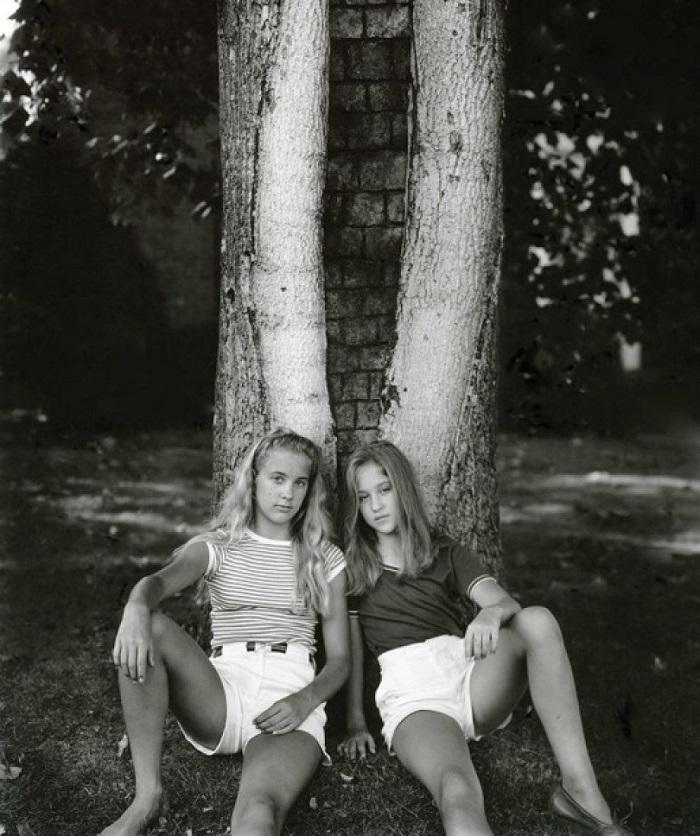 Dos niñas de 12 años sentadas contra el tronco de un árbol cuyo hueco recuerda a una vagina. Foto de Sally Mann para el libro At Tweelve