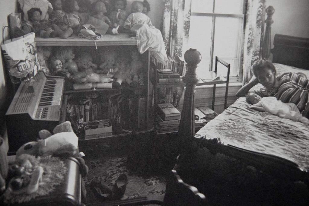 Niña de 12 años madre adolescente tumbada en la cama junto a un bebé en una habitación llena de muñecas- Foto de Sally Mann para el libro At Twelve.