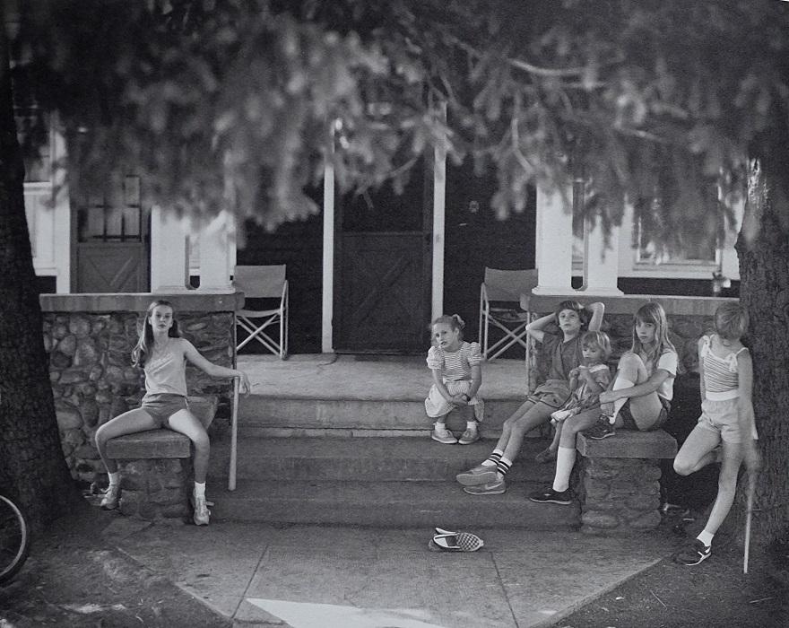 Niña de 12 años y grupo de niños menores en las escaleras de entrada de una casa. Foto de Sally Mann para el libro At Twelve.