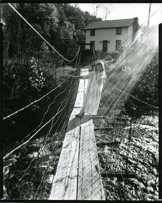 Niña de 12 años vestiuda con un camisón en un puente de cuerdas sobre un río y un rayo de sol cayendo sobre ella. Foto de Sally Mann para el libro At Twelve.