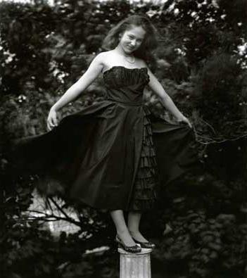 Niña de 12 años subida en un pedestal con un vestido para un baile. Foto de Sally Mann para el libro At Twelve.