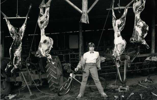 Niña de 12 años que parece un chico vestida con traje y pajarita posa poyada en una bici y rodeada de cuerpos de ciervos desollados que cuelgan del techo. Foto de Sally Mann para el libro At Twelve.