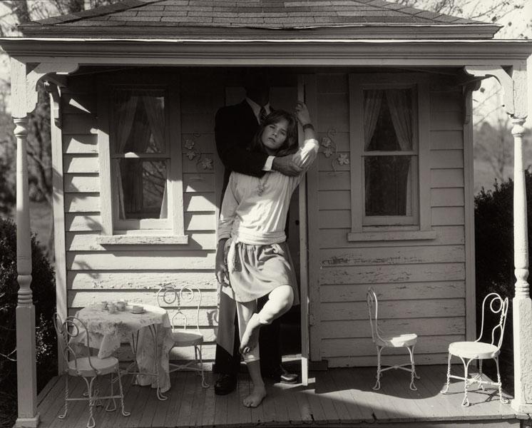 Niña de 12 años posa de pie en el porche de su casa con su padre agarrándola por detrás fotografiada por Sally Mann para el libro At Twelve