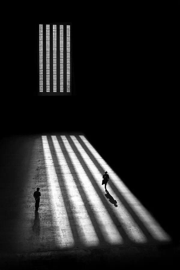 Fotografía de una mujer y un hombre caminando en una sala oscura e iluminados por los rayos del sol que entran por un gran ventanal. Foto de Alan Schaller.