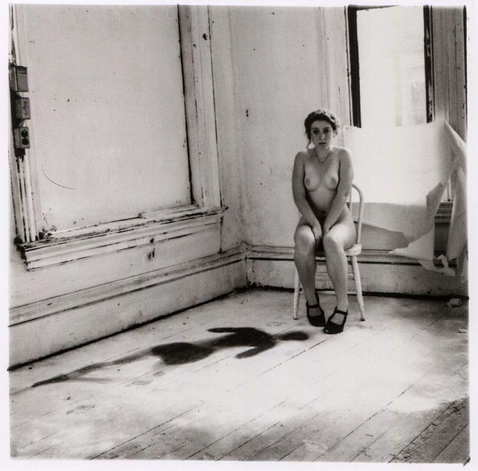 Autorretrato de Francesca Woodman posando desnuda sentada en una silla frente a su silueta impresa en harina en el suelo