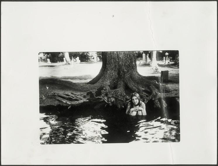Autorretrato de Francesca Woodman desnuda y metida en el agua frente a un árbol al que se le ven las raíces
