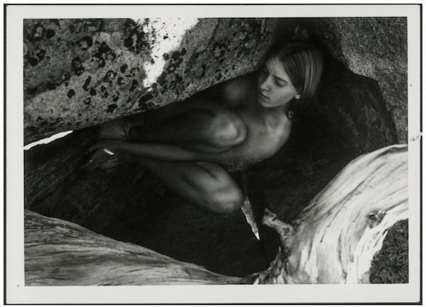 Autorretrato de Francesca Woodman posando desnuda en el hueco de un tronco de árbol