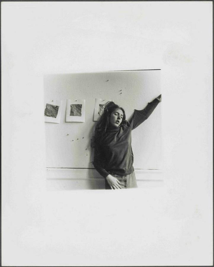Autorretrato de Francesca Woodman con un brazo sujeto con chinchetas en la pared