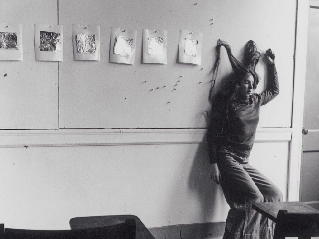 Francesca Woodman apoyada en una pared con su mechones d e pelo sujetos con chinchetas. Foto: George Lange.