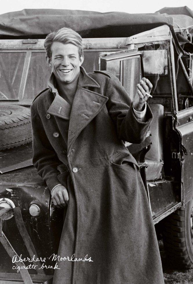 El fotógrafo Peter Beard, de joven, posa apoyado en un una camioneta y con un cigarro en la mano